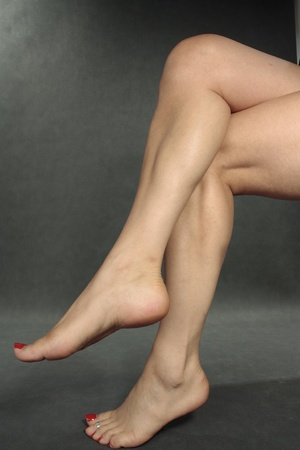 female feet: Woman legs feet  over grey background Stock Photo
