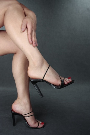 Beautiful woman legs black shoes  over grey Stock Photo - 10503436
