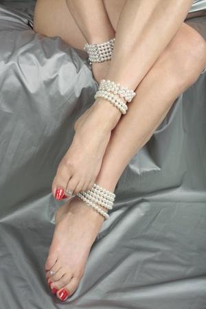 sexy füsse: Schöne Frau Beine mit Perlen in Silber satin fabric