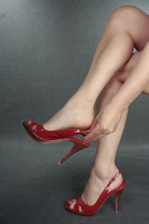 Beautiful woman legs putting on red shoes  over grey Stock Photo - 10850634