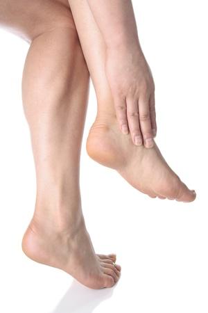 waxed: Mujer masajear los pies doloridos sobre fondo blanco Foto de archivo