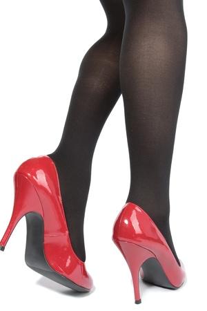 tacones rojos: Mallas de piernas de hermosa mujer con tacones rojos sobre fondo blanco