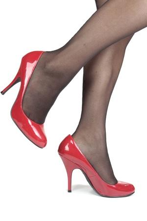 tacones rojos: Hermosas piernas medias de mujer con tacones rojos sobre fondo blanco Foto de archivo