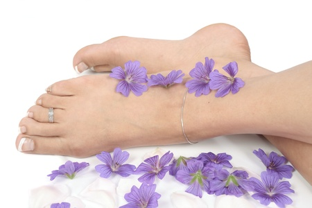 sensual massage: Woman  legs and flowers  over white background