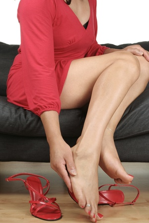 female feet: Woman legs massaging aching feet with shoes