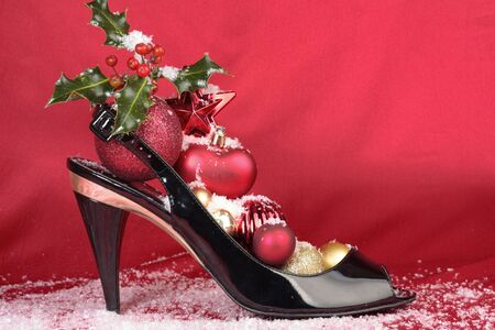 Ladies shoes with christmas decorations over red background Stock Photo - 11546397