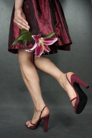 Woman legs with red satin dress and flowers  over grey photo