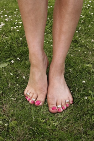 female feet: Female feet on grass lawn with flowers Stock Photo