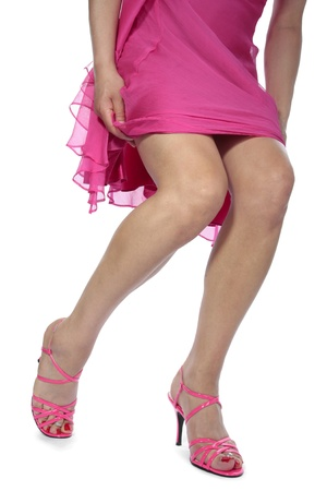 Beautyful woman legs with pink dress and heels over white photo
