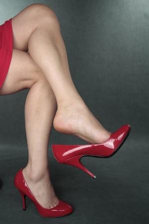 tacones rojos: Piernas hermosas de la mujer wering tacones rojos sobre gris