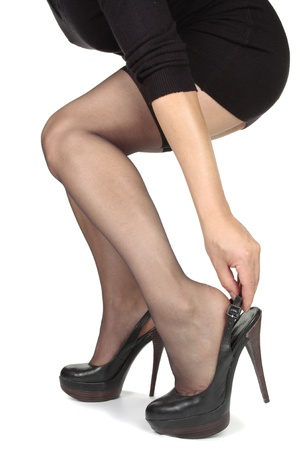 Woman legs  putting on heels  shoes over white Stock Photo - 11594883