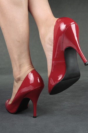 waxed: Beautiful female legs wearing red heels over grey background Stock Photo