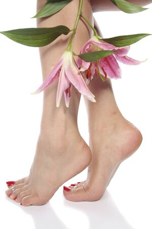 waxed: Female feet with flowers isolated over white background