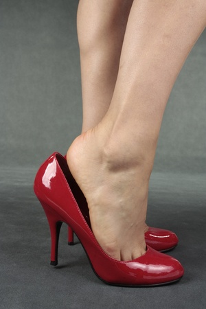 Beautiful female legs wearing red heels over grey background photo