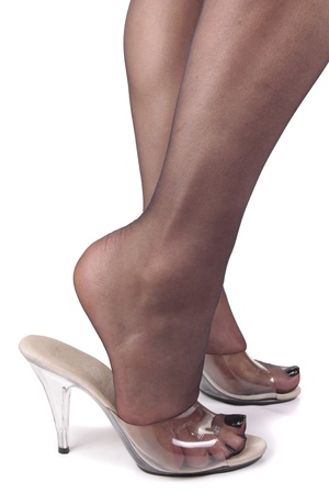 Femal legs wearing tights and clear high heels over white background photo