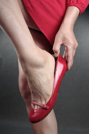 Woman putting on red flat shoes over grey photo