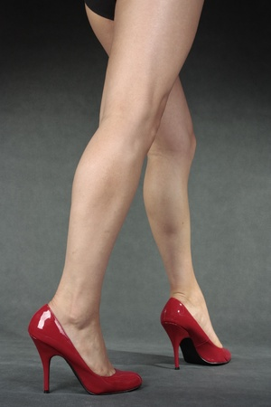 Beautiful woman legs wering  red heels over grey Stock Photo - 12711761