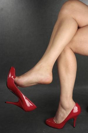 tacones rojos: Piernas de mujer con tacones rojos sobre fondo gris
