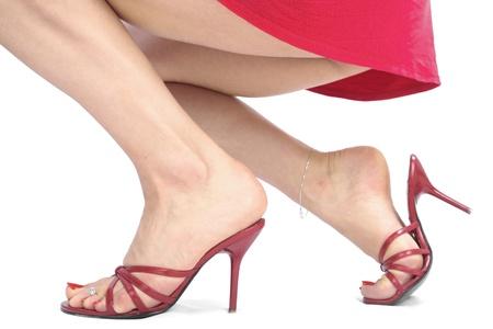 waxed legs: Piedi femminili che indossano scarpe tacco rosse isolato su sfondo bianco