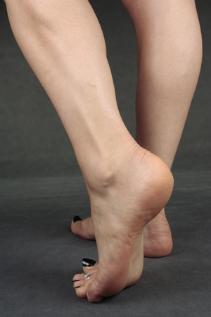 waxed: Female feet over grey background