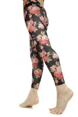 Female legs wearing floral leggings over white background