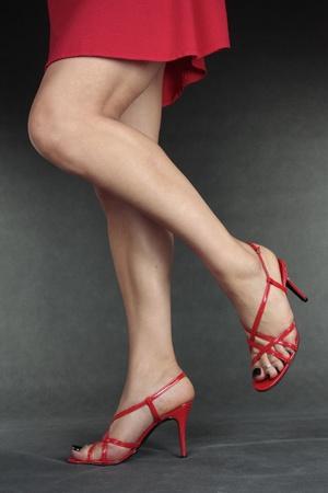 Beautiful woman legs wearing  red heels over grey photo