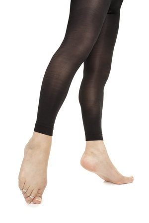 hold ups: Woman legs wearing footless black tights over white background