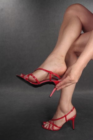 Woman legs putiing on red heels   over grey background Stock Photo