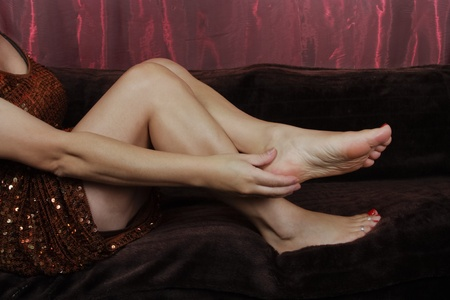 aching: Woman massaging aching feet over white background