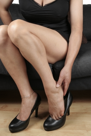 female feet: Woman massaging aching feet over white background