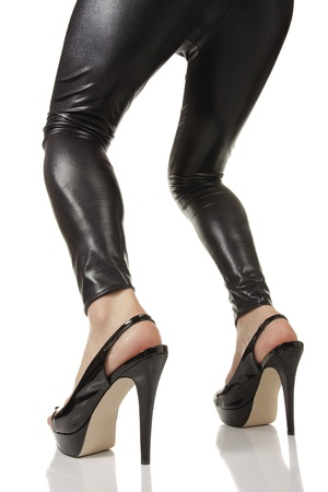 hold ups: Female legs wearing black leggings and heels over white background