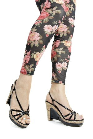 hold ups: Female legs wearing floral leggings and heels over white background