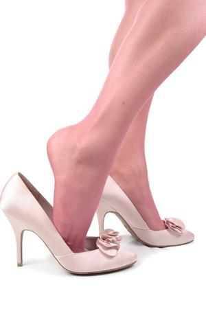 Female legs wearing satin high heel shoes and tights isolated over white background photo
