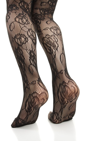 hold ups: Woman legs wearing black lace tights over white background