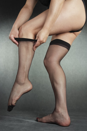hold ups: Woman putting on black hold-ups over grey background