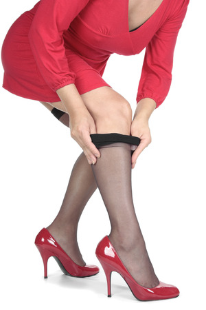 hold ups: Woman in red dress putting on stockings