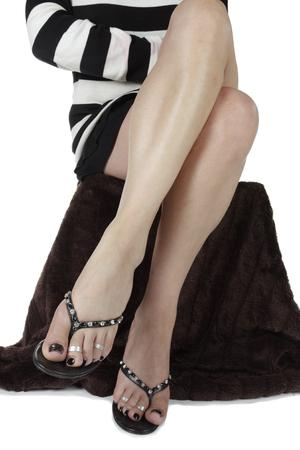 tacones negros: Mujer sentada con un vestido corto y tacones negros Foto de archivo