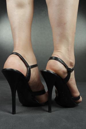 tacones negros: Piernas de mujer con tacones negros sobre gris