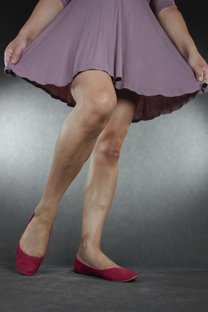 Woman legs and feet wearing purple dress and shoes over grey background photo