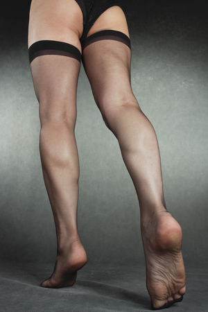 hold ups: Woman legs wearing black hold-ups over grey background Stock Photo
