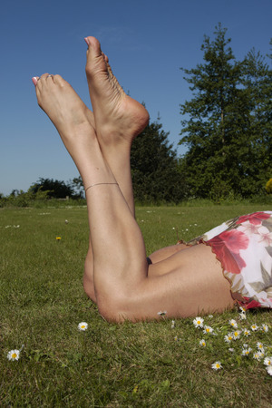toes: Female legs relaxing on grass lawn with flowers Stock Photo