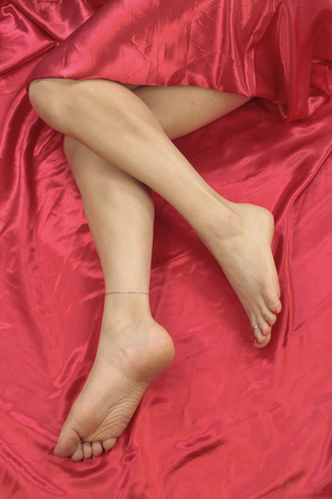 waxed legs: Female feet and legs over red background