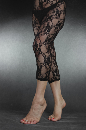 female soles: Woman legs wearing black lace leggins over grey background