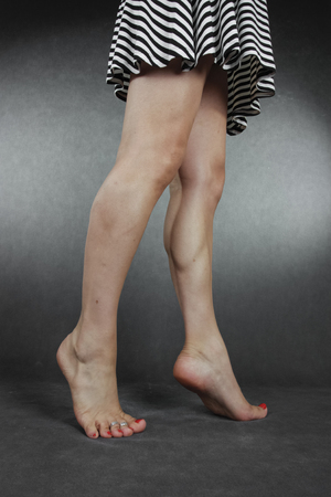 waxed legs: Woman legs and feet wearing  dress  over grey background