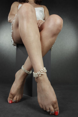 Woman legs and feet sitting over grey background