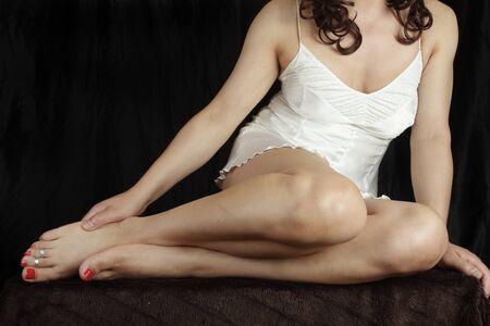 nightie: woman sitting wearing white nightie over grey background Stock Photo