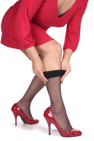 undress: Woman in red dress putting on stockings