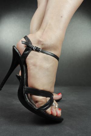 footware: Woman legs wearing black heels over grey Stock Photo