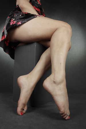 waxed legs: Woman legs and feet sitting over grey background