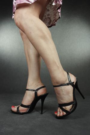 black heels: Woman legs wearing black heels over grey Stock Photo